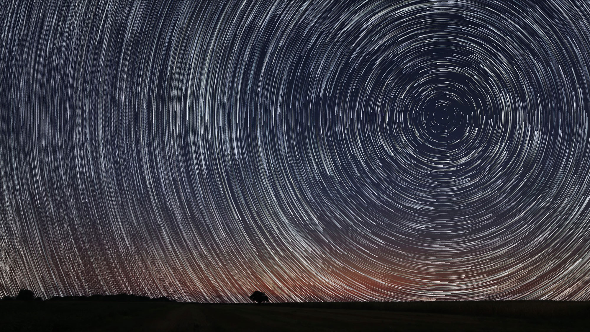Due to Earth's rotation, the sun, moon, and stars appear in different places in the sky each day. Here, the apparent motion of the stars results in a unique glow across the night sky.