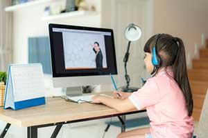 Girl listening to her teacher on a computer