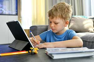 Boy doing his homework at home as part of the flipped classroom blended learning model